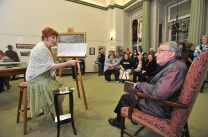 Carol and Rock Palmer of Westfield portray the parts of Florence Rand Lang and Henry Lang as they perform a skit Saturday evening at the Westfield Athenaeum's 150th celebratory open house. The skit portrayed the couple's presumed conversation as they discussed the request for a $50,000 contribution to the Athenaeum which ultimately funded the Jasper Rand Art Gallery and the Lang Auditorium. (Photo ©2014 Carl E. Hartdegen)