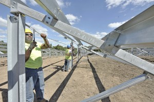 Jeremy Bobo, foreground, of Synergy Solar, and Tony Paton, background, of Elm Electric, use heavy steel cables to square a solar panel mount at the new seven-acre solar farm near the Big-Y supermarket in Southwick on Wednesday. (Photo by Frederick Gore)