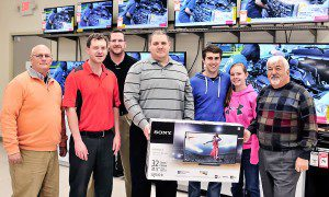 """Matt Kidrick, third from right, and his fiancee, Jen Balukonis, receive their 32-inch Sony television from Manny's TV & Appliances owner Manny Rovithis, far right, and his team of local employees for winning our pro football contest, """"Beat 'The Putz'"""". Matt accepted the grand prize for his grandfather, Robert, who was not available at the time of the presentation. (Photo by Frederick Gore)"""