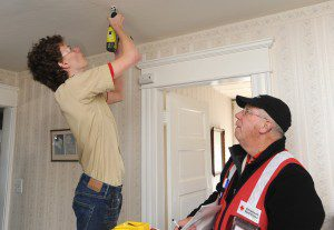 Red Cross volunteer Dan Cawrse supervises as boy scout Nick Bergeron of Southwick's Boy Scout Troop 338 installs a smoke detector bracket in the home of a city resident Saturday morning. (Photo by Carl E. Hartdegen)