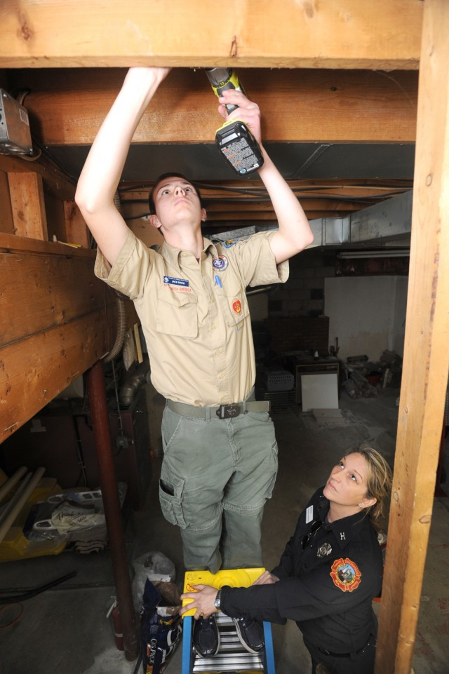 Westfield Fire Captain Rebecca Boutin holds the ladder as Boy Scout Jack Davis of Southwick's Boy Scout Troop 338 installs a carbon monoxide detector in the basement of a city resident Saturday morning. (Photo by Carl E. Hartdegen)