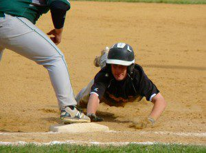 Tigers' base runner Nick Clegg, right, slides back safely into first base. (Photo by Chris Putz)