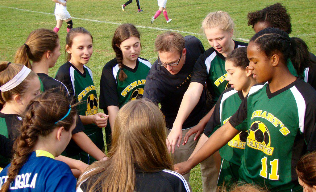 The St. Mary Saints bow their heads in a group prayer prior to taking the field against Renaissance in a high school girls' soccer game Thursday at Marshall Roy Field in Springfield. (Photo by Chris Putz)
