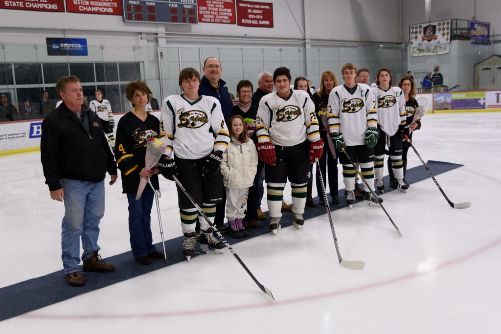 St. Mary's senior boys' ice hockey players enjoy a special moment out on the ice alongside family members during pregame festivities Friday night at Amelia Park Ice Arena. (Photo by Marc St. Onge)