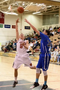 Westfield's John O'Brien (5) launches a one-handed floater in the lane over the arm of a West Springfield player Monday night. (Photo by Marc St. Onge)