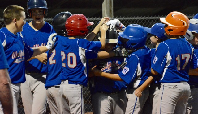 Teammates swarm Westfield American's Jeremy McCormick after McCormick blasted a two-run home run Thursday night in Belchertown. (Photo by Chris Putz)