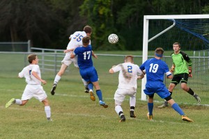 Joseph Coon tries to head the ball into Palmer's goal with the help of Aaron Trask and Jayden Marge Wednesday night in Huntington. (Photo by Marc St. Onge)